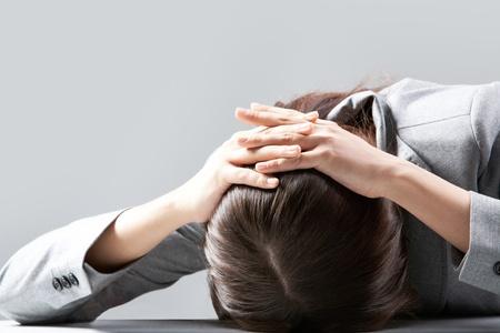 fille triste: Une jeune femme se cachant son visage sur table