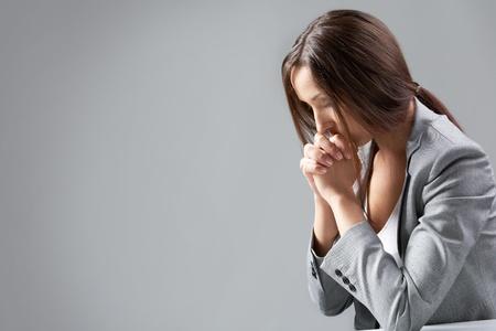 mujer orando: Una mujer sentada a la mesa y orando