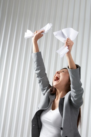 A depressed woman raising her hands with crumpled paper and screaming photo