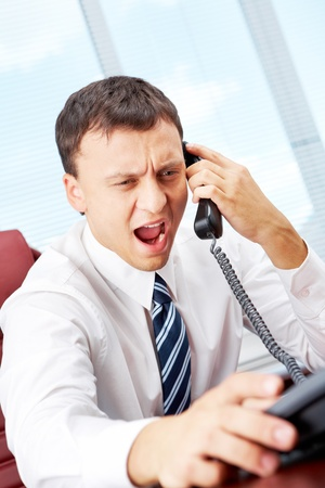 A manager sitting at table and shouting in telephone receiver Stock Photo - 9571904
