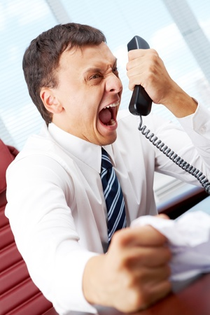 angry boss: An angry manager screaming in telephone receiver