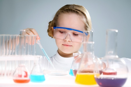 A little girl analyzing chemical liquid   photo