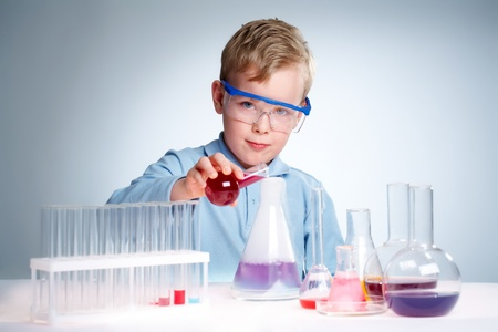 A little boy pouring liquid into a flask and looking at camera  photo