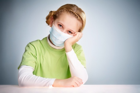 A little girl sitting in protective mask photo