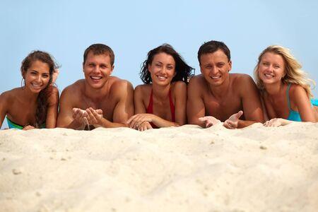 sunbathing: Portrait of happy girls and guys lying on sand on summer vacation Stock Photo