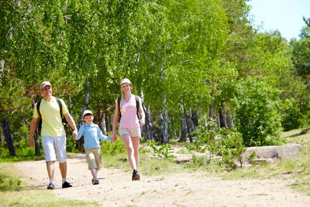go: Portrait of three family members walking down road at summer