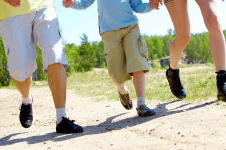 Legs of three family members going down forest path during summer vacation photo