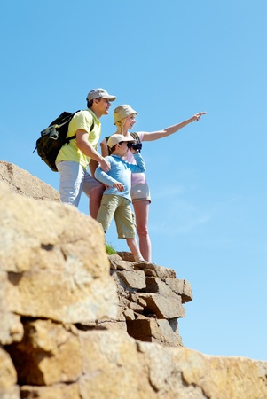 Portrait of family members looking afar outside while standing on cliff photo