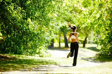 jogging in park: A young girl jogging in the park along trees Stock Photo