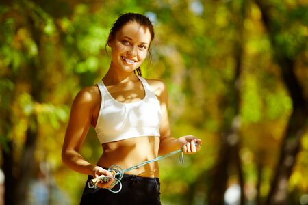 A young woman holding a skipping rope, looking at camera and smiling against natural background    photo