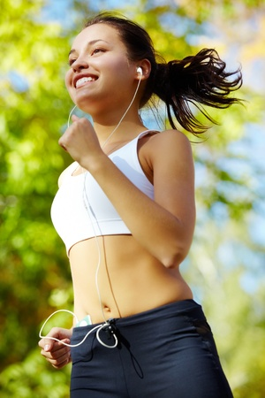 Portrait of a young woman jogging with a walkman Stock Photo