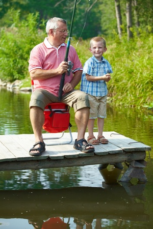 Photo of grandfather and grandson fishing in natural environment photo