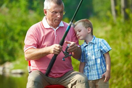Photo of grandfather and grandson fishing on weekend photo