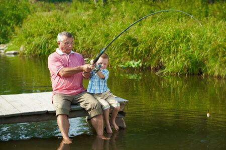 fishing lure: Photo of grandfather and grandson pulling rod while fishing on weekend Stock Photo