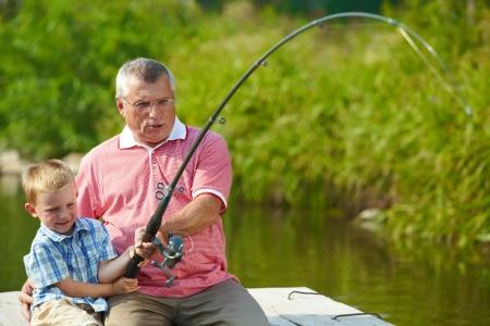 hombre pescando: Foto del abuelo y nieto tirando varilla juntos durante la pesca