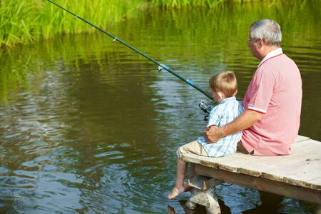 angler: Photo of grandfather and grandson sitting on pontoon and fishing on weekend Stock Photo