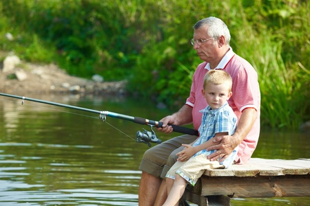 Photo of grandfather and grandson sitting on pontoon and fishing on weekend photo