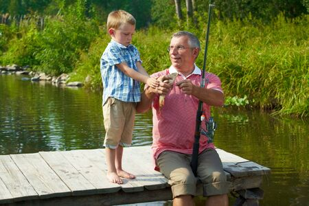 Photo of grandson looking at fish caught by his grandfather photo