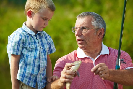 Photo of grandfather telling his grandson about the fish caught by them photo