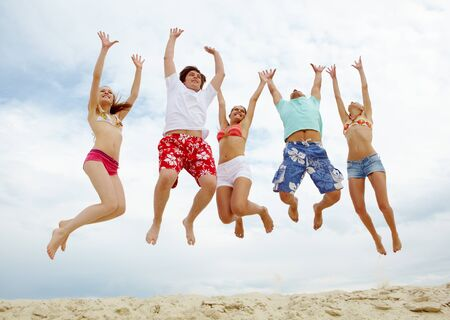 Photo of five friends in high jump over sandy beach photo