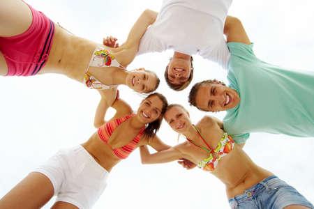Below view of joyful teens looking at camera with smiles photo