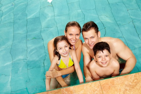 Photo of happy family in swimming pool smiling at camera Stock Photo - 9572137
