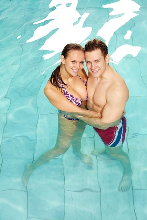 Photo of happy couple in swimming pool embracing and looking at camera  photo