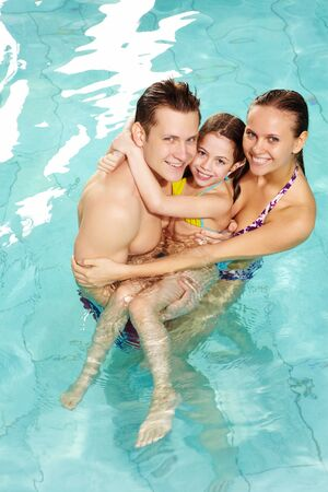 Photo of happy family of parents and cute daughter in swimming pool  photo