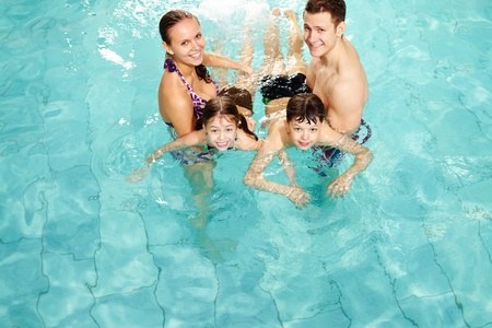 Photo of happy family in swimming pool smiling at camera  photo