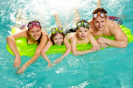 girl swimming: Cheerful family in swimming pool smiling at camera  Stock Photo