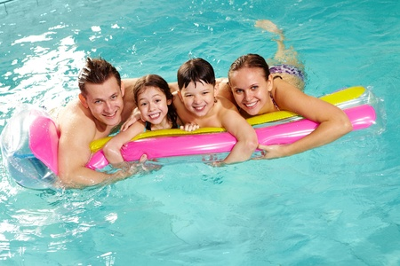family swimming: Cheerful family in swimming pool having nice time