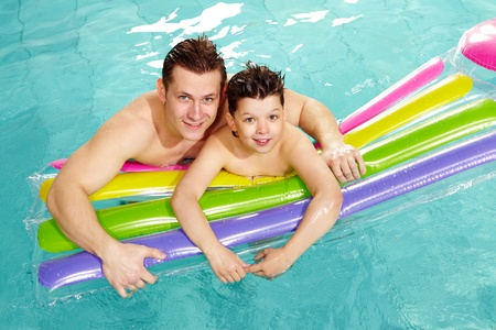 lad: Photo of happy lad and his father in water  Stock Photo