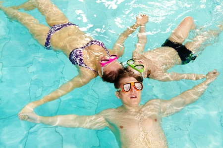 Photo of parents and their son in goggles holding by hands in water  photo