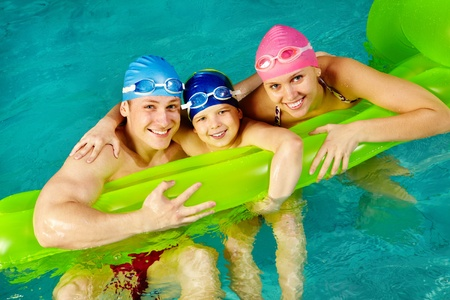 Photo of happy family of swimmers smiling at camera  photo