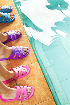 Three pairs of feet in flipflops in swimming pool photo