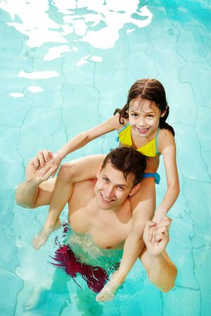 swimwear: Photo of happy girl sitting on her father shoulders in pool