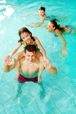 Photo of happy girl sitting on her father shoulders in pool with swimming boy and mother on background photo
