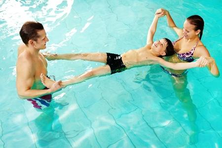 Photo of happy parents teaching their son how to swim  photo