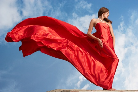 red scarf: Photo of graceful female folded in bright red silk shawl with cloudy sky at background Stock Photo