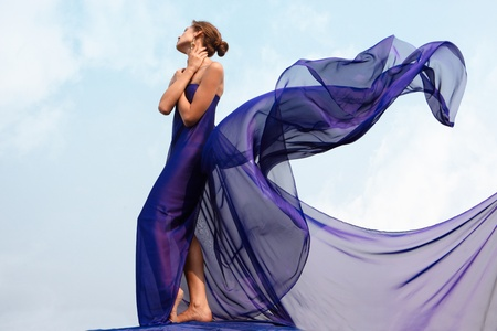 feminine: Photo of graceful female folded in dark blue chiffon shawl with cloudy sky at background Stock Photo