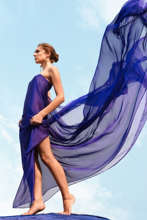 free background: Photo of graceful female folded in dark blue chiffon shawl with cloudy sky at background Stock Photo