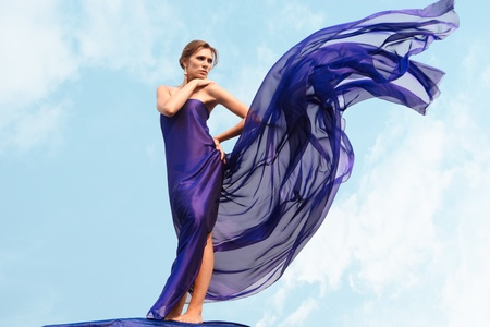 Charming woman folded in dark blue chiffon shawl with cloudy sky at background photo