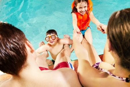 kids swimming pool: Cheerful kids playing with parents in swimming pool