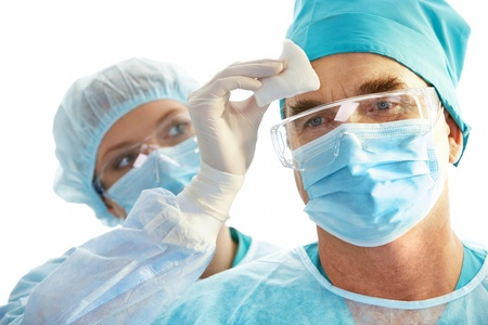 surgical glove: Image of surgeon during work with his forehead being rubbed by nurse