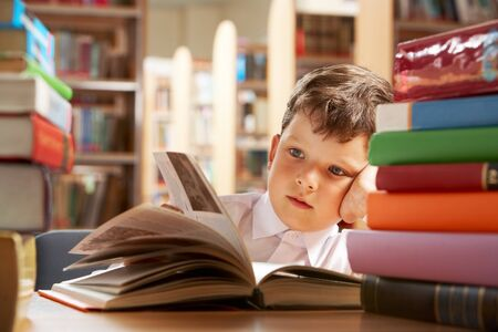 keen: Close-up of cute boy reading book while preparing for lesson in library Stock Photo