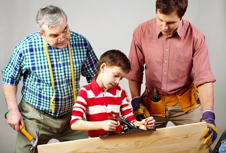 A boy working with plane under his father and grandpa�s supervision photo