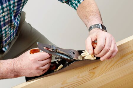 carpenter items: Hands of carpenter working with plane and plank