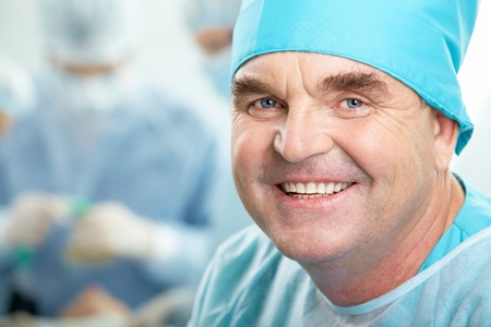 Portrait of confident senior surgeon looking at camera on background of working group photo