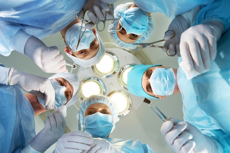 surgeon operating: Below view of surgeons holding medical instruments in hands and looking at patient