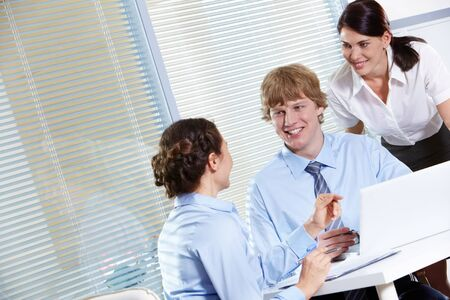 Portrait of friendly workteam discussing project in the office Stock Photo - 9572208